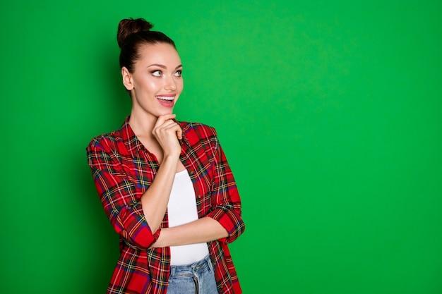 Foto de menina alegre positiva tocando o queixo dedos olhar copyspace pensar pensamentos aproveite férias de verão plano usar camisa xadrez isolada sobre fundo de cor brilhante