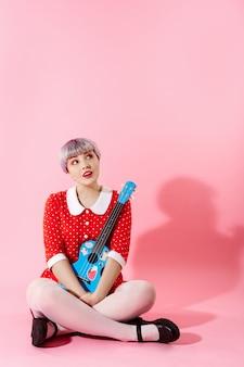 Foto de menina bonitinha bonita com cabelo violeta claro curto, vestido vermelho, segurando o ukulele azul sobre parede rosa