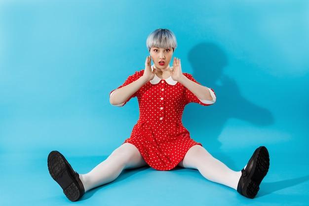 Foto de menina bonitinha bonita com cabelo violeta claro curto, vestido vermelho sobre parede azul