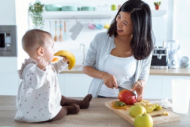 Foto de menina bonitinha brincando com comida enquanto a mãe corta frutas para preparar mingau de bebê na cozinha.