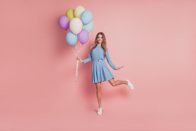 Foto de menina brincalhona com balões de ar coloridos em sapatilhas de saia curta em fundo rosa