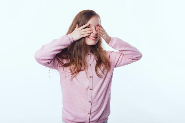 Foto de menina cobrindo os olhos com as palmas das mãos e olhando através deles