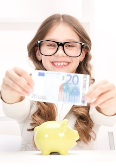 Foto de menina com cofrinho e dinheiro