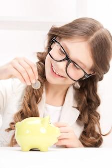 Foto de menina com cofrinho e moeda