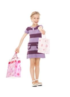 Foto de menina com sacolas de compras.