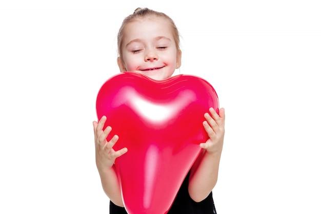 Foto de menina em um vestido preto elegante segurando um balão vermelho em forma de coração