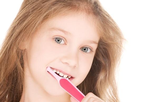 Foto de menina feliz com escova de dentes sobre branco