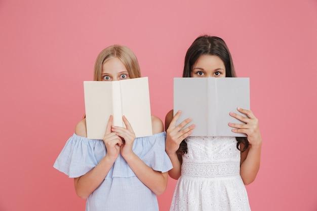 Foto de meninas europeias excitadas ou assustadas, de 8 a 10 anos, usando vestidos cobrindo o rosto com livros, isolado sobre um fundo rosa