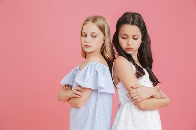 Foto de meninas morenas e loiras de 8 a 10 anos de idade usando vestidos de costas um para o outro com os braços cruzados e expressando briga, isolada sobre um fundo rosa
