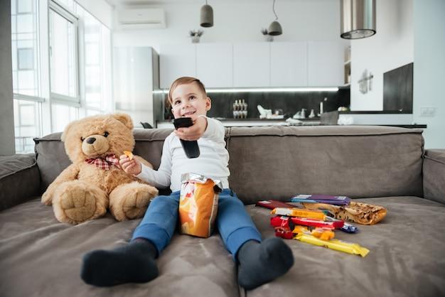 Foto de menino alegre sentado no sofá com o ursinho de pelúcia em casa e assistindo tv enquanto come batatinhas. segurando o controle remoto.