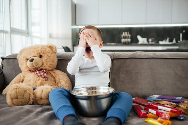 Foto de menino assustado no sofá com o ursinho de pelúcia em casa assistindo tv enquanto come batatas fritas.