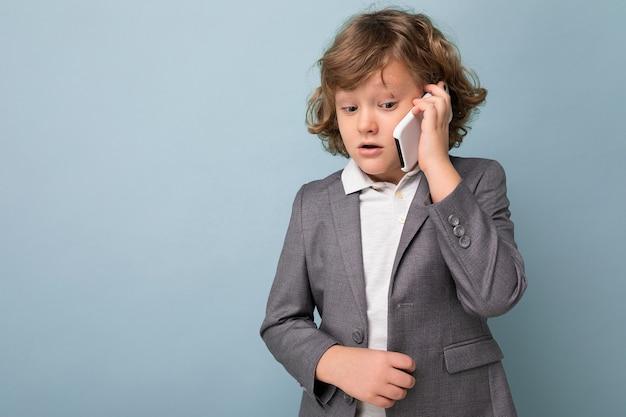 Foto de menino bonito com cabelo encaracolado, vestindo um terno cinza, segurando e usando o telefone