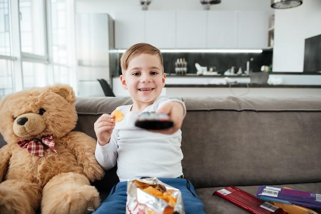 Foto de menino bonito sentado no sofá com o ursinho de pelúcia em casa e assistindo tv enquanto come batatas fritas. segurando o controle remoto.