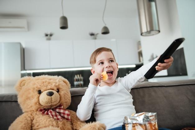 Foto de menino brincalhão sentado no sofá com o ursinho de pelúcia em casa e assistindo tv enquanto come batatinhas. segurando o controle remoto.