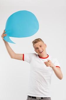 Foto de menino caucasiano hipster segurando o balão de pensamento em branco acima de sua cabeça e gesticulando significado dedo ei, você isolado no branco
