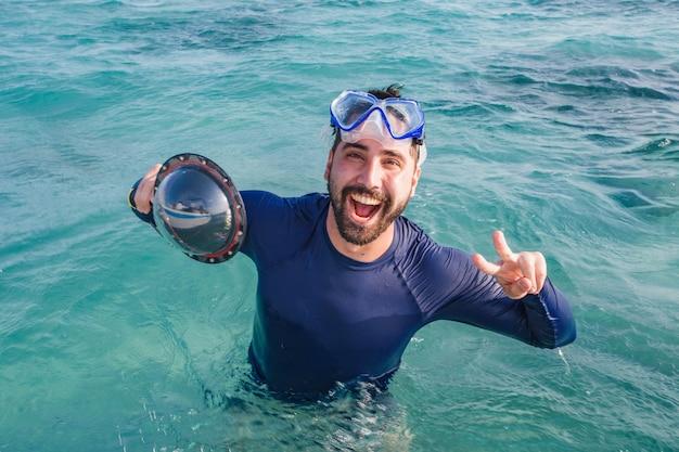 Foto de menino de férias com óculos de natação no mar. homem de férias curtindo o oceano
