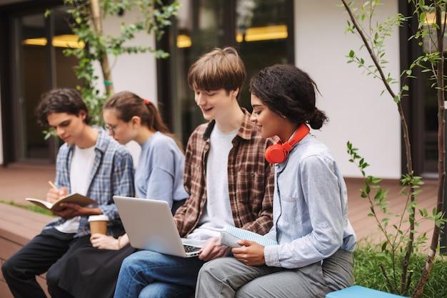 Foto de menino e menina sentados no banco e usando o laptop enquanto passam algum tempo no pátio da universidade