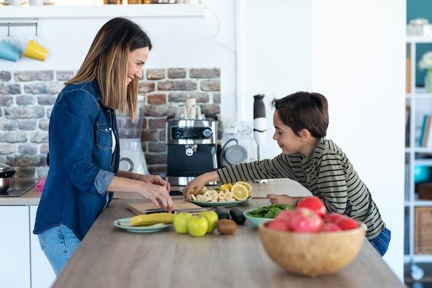 Foto de menino pegando uma fatia de banana enquanto sua mãe o olha e sorri na cozinha de casa.