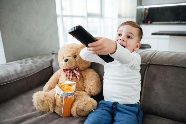 Foto de menino sentado no sofá com o ursinho de pelúcia em casa e assistindo tv enquanto come batatinhas. segurando o controle remoto.