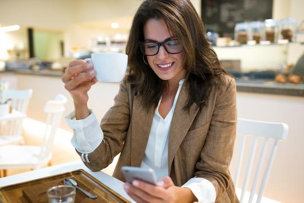 Foto de mensagens de texto de jovem empresária sorridente com seu telefone celular no café.