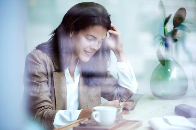 Foto de mensagens de texto inteligente jovem empresária com seu telefone celular no café.
