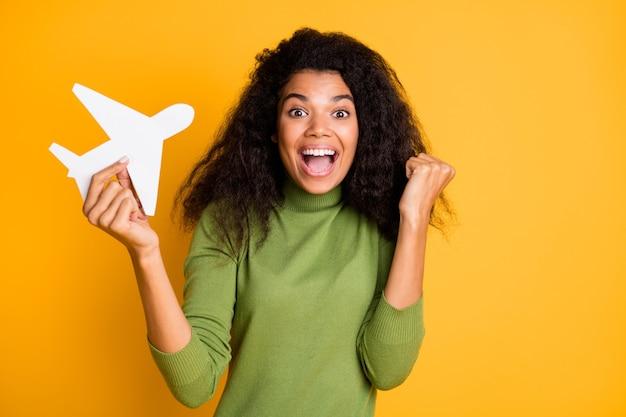 Foto de mestiça positiva fofa linda garota ganhou ingressos para viajar para o exterior de avião regozijando emoções animadas segurando avião isolado encaracolado ondulado amarelo cor de fundo vívida