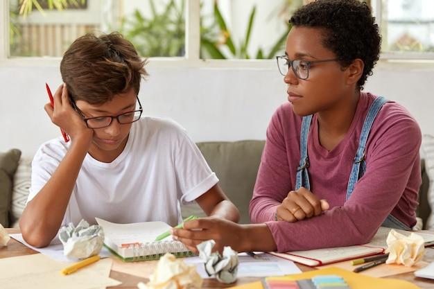 Foto de mestiço rapaz e mulher sentam-se juntos no local de trabalho, discutem ideias para o projeto, usam óculos. mulher negra com piercing explica algo ao irmão, indica por escrito no diário.