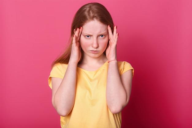Foto de metade do comprimento da menina adolescente triste com dor de cabeça terrível, tem sérios problemas na escola, veste casualmente, posando em rosa. expressões faciais e conceito de emoções de pessoas.