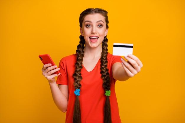 Foto de moça bonita segurando telefone mostrando novo cartão de crédito do banco