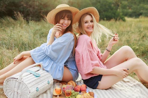 Foto de moda ao ar livre de duas mulheres atraentes com chapéu de palha e roupas de verão desfrutando de piknik.