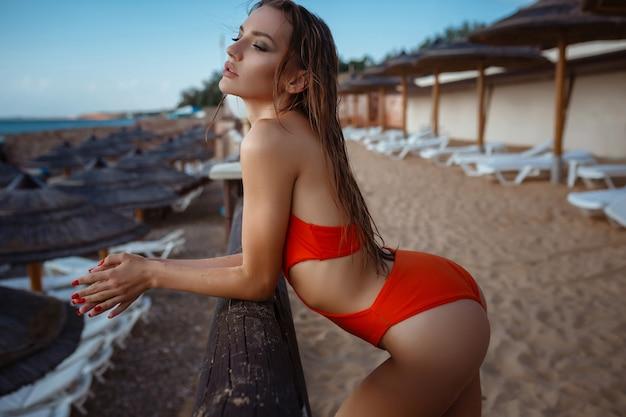 Foto de moda ao ar livre de linda mulher sensual com longos cabelos escuros em um elegante maiô laranja relaxante ao lado da piscina