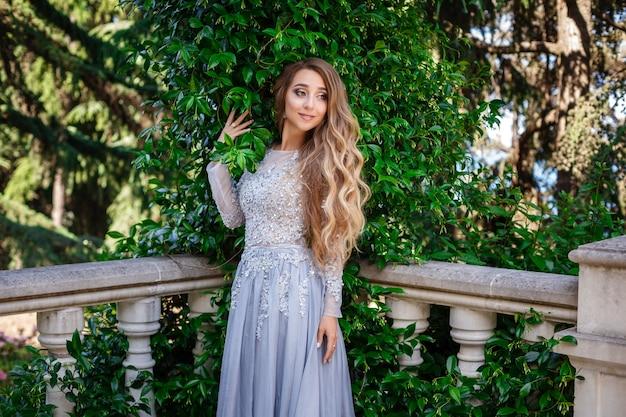 Foto de moda ao ar livre de mulher bonita e elegante com cabelo loiro em vestido de lantejoulas luxuosas e acessórios prateados, posando no parque de verão