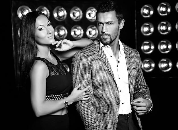 Foto de moda de homem elegante bonito de terno com bela mulher sexy, posando em fundo preto luzes de estúdio