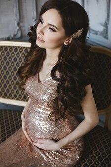 Foto de moda de luxo de uma jovem grávida em um vestido de noite brilhante.