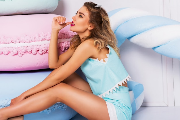 Foto de moda de mulher bonita sexy com penteado encaracolado loiro, vestindo blusa de couro azul na moda e shorts perto de doces grandes adereços coloridos. na moda jovem moderna em tons pastel.