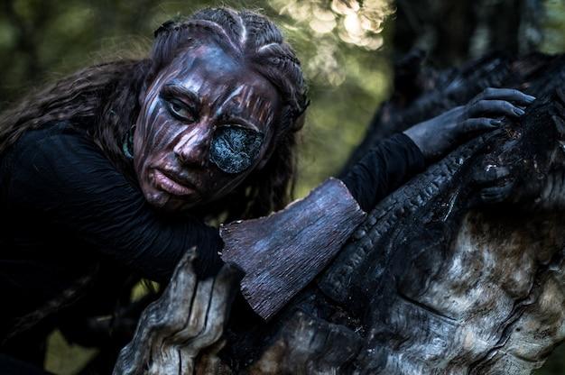 Foto de moda de mulher com maquiagem criativa em uma floresta. fantasia.