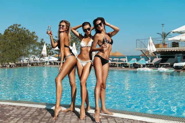 Foto de moda de mulheres lindas sexy em biquíni preto relaxando ao lado de uma piscina