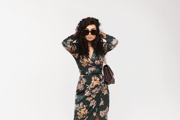 Foto de moda de uma bela jovem em um lindo vestido com flores posando sobre fundo branco Foto Premium