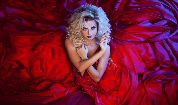 Foto de moda jovem mulher magnífica no vestido vermelho. retrato de estúdio