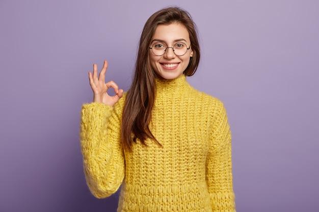 Foto de modelo feminina européia positiva faz gesto de aprovação, concorda com ideia bonita
