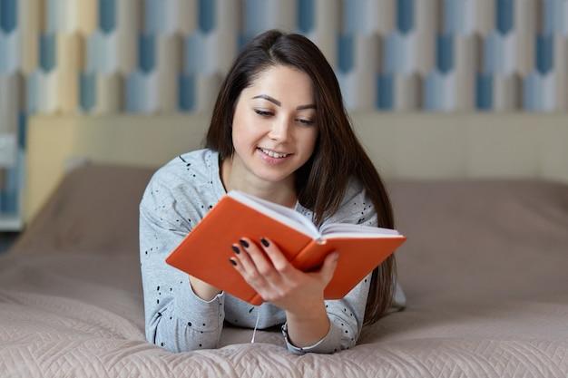 Foto de modelo feminino caucasiano relaxado lê livro vermelho, tem um sorriso gentil no rosto, goza de boa trama da história, vestida de jumper casual