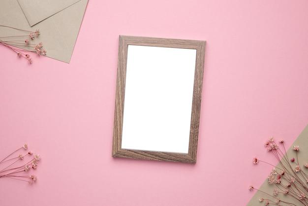 Foto de moldura de madeira de maquete com flor seca na vista superior do fundo rosa