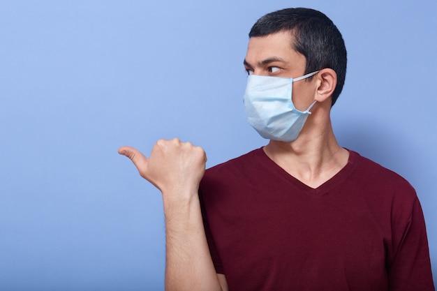 Foto de morena confiante cuidadosa, olhando de lado, mostrando a direção com o polegar, usando máscara antibacteriana, estando em quarentena, aderindo às medidas de proteção. copyspace para propaganda.