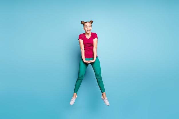 Foto de morena de cabelos castanhos linda namorada atraente pulando vestindo calça verde calça calça expressando emoções entusiasmadas isoladas sobre parede azul pastel