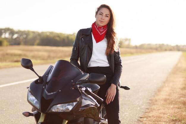 Foto de motociclista feminina despreocupada, vestida com roupas da moda
