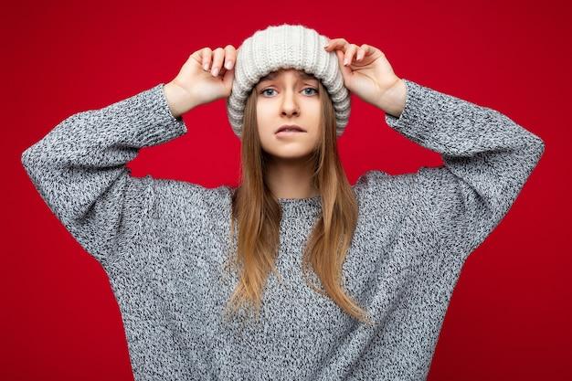 Foto de muito emocional jovem loira escura em pé isolado sobre a parede de fundo vermelho, vestindo um suéter cinza e um chapéu bege, olhando para a câmera e se preocupando.