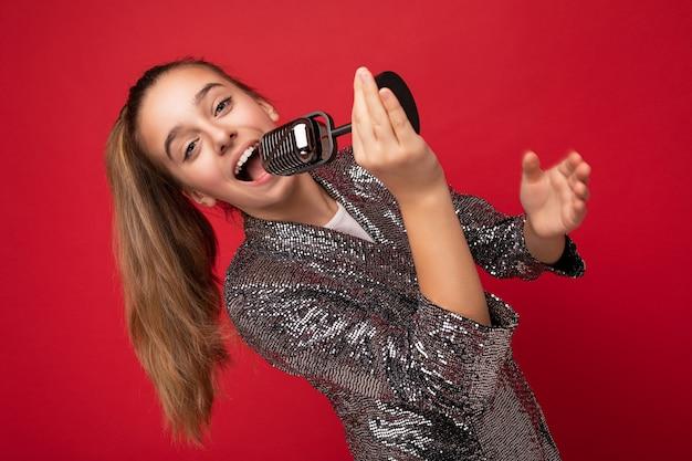 Foto de muito feliz positiva morena garotinha usando vestido elegante brilho em pé isolado sobre a parede de fundo vermelho, cantando a música para o microfone de prata, olhando para a câmera.