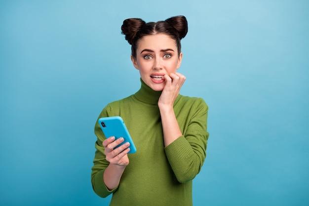 Foto de mulher adolescente assustada e chocada, mordendo os dedos, os dentes, navegando no telefone, leia os comentários negativos da postagem do blog, use uma gola verde isolada na parede azul