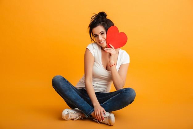 Foto de mulher adolescente romântica 20 anos em roupas casuais, sentado com as pernas cruzadas no chão e segurando o coração de papel vermelho perto do rosto, parede amarela