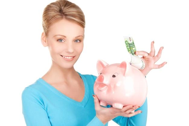 Foto de mulher adorável com cofrinho e dinheiro